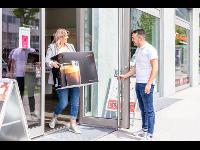 Eine glückliche Kundin verlässt den JURA Store