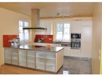 Küche weiß lackiert mit Glasrückwand in oranger Farbe
