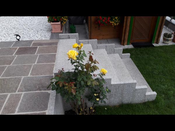Granit Blockstufen in Kombination mit Porphyr Plasterplatten und weißem Zierkies