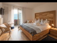 Doppelzimmer mit Holzbett und Aussicht im Kleinhofers Himbeernest in Anger in der Steiermark