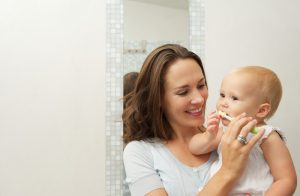 smiling mother teaching cute baby how to brush teeth with toothbrush