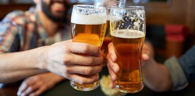 Drei Freunde stoßen mit ihren Biergläsern an