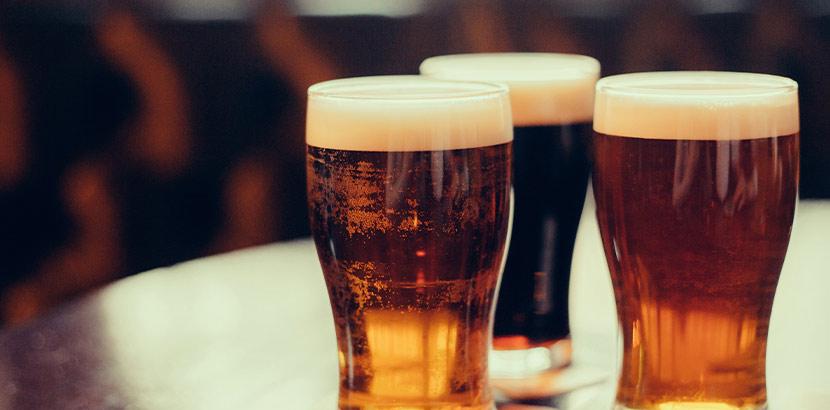 Drei Biergläser mit unterschiedlichen Biersorten auf einem Tisch