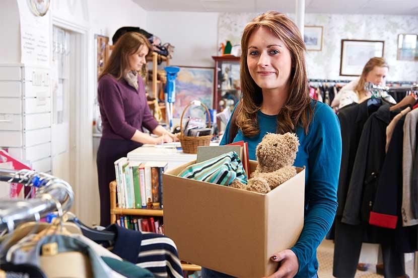 Junge Frau, die einen Karton mit Kleidung in einen Second Hand Shop bringt. Second Hand Wien.