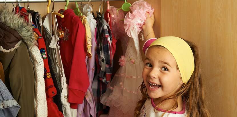 Kleines lachendes Mädchen im Kinder Secondhandladen in Wien.