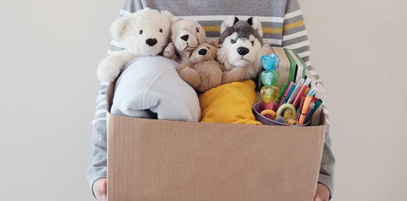 Teeanger, der einen Karton mit gebrauchtem Spielzeug in einen Kinder Secondhand Shop in Wien bringt.