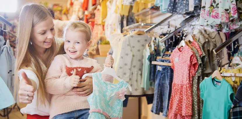Junge Mutter mit kleiner Tochter beim Shoppen im Secondhand Kinder Wien Shop.