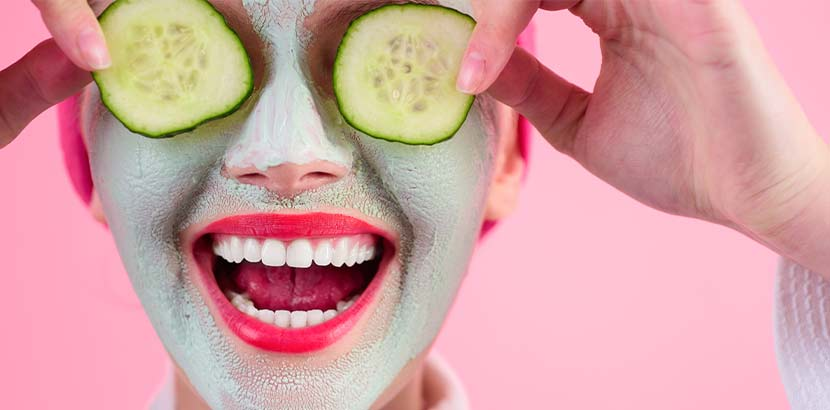 Junge Frau mit Gurkenscheiben auf den Augen, die als Augenringe Hausmittel gelten.