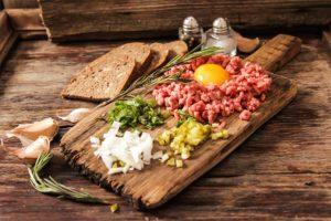 Alle schmackhaften Zutaten für Beef Tartar auf einem Holzbrett angerichtet.