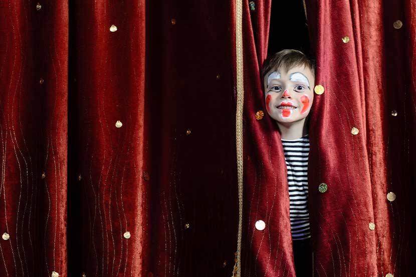 Kleiner Junge mit geschminktem Clownsgesicht, der im Kindertheater Wien durch den Vorhang auf der Bühne schaut.