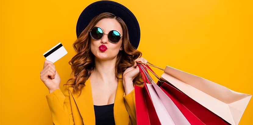 Hübsche brünette Shopaholic mit vielen bunten Einkaufstaschen und einer Kreditkarte.
