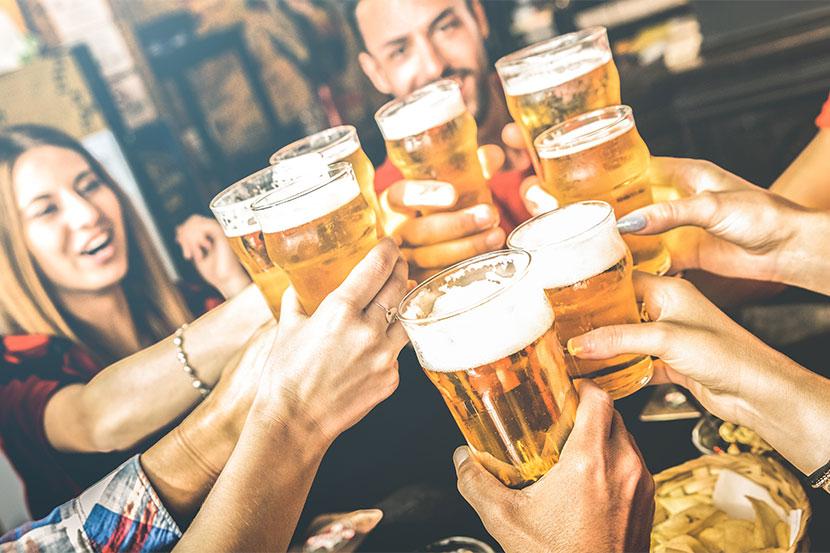 Gruppe von jungen Menschen, die in einem Pub mit Bier anstoßen. Bierlokal Wien.