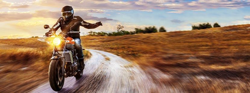 A-Führerschein: Ein Mann sitzt auf einem Motorrad und fährt durch eine wilde Landschaft.