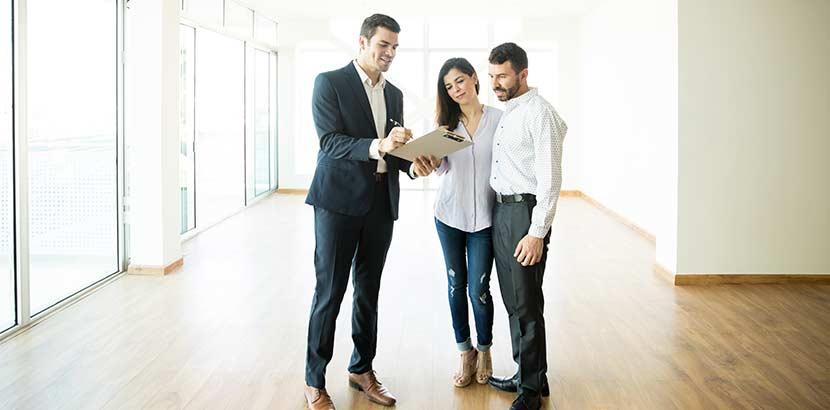 Gut gebauter Immobilienmakler, der mit einem interessierten Paar die Konditionen des Mietvertrages durchgeht. Aufgaben Immobilienmakler Wien.