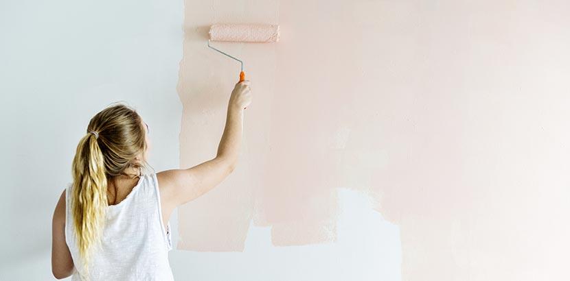 Frau streicht Wand