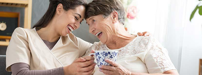 Eine Pflegerin trinkt zusammen mit einer älteren Dame eine Tasse Tee im Pflegeheim. Beide lachen.