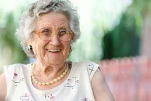 Eine ältere, lachende Frau in einem Pflegeheim.