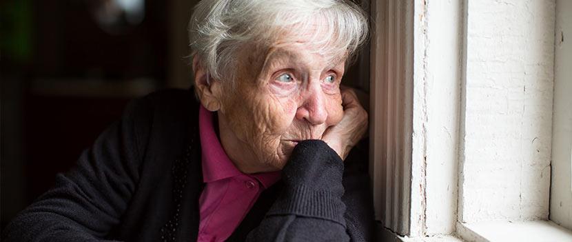 Pflegeheim und Altenheim: Eine alte Frau schaut nachdenklich aus dem Fenster.