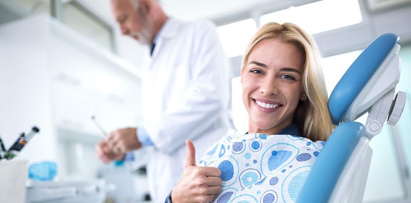 Junge blonde Frau beim Zahnarzt, die sich darüber freut, dass sie ihre Zahnarztangst überwunden hat.