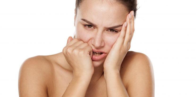Junge Frau mit Zungenbrennen sucht Hausmittel die helfen Symptome zu lindern und vermeiden.