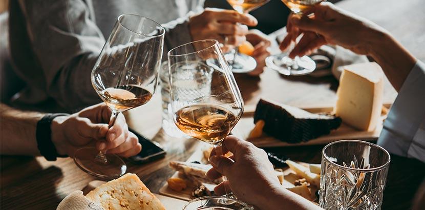 Leute stoßen mit Orange Wine an