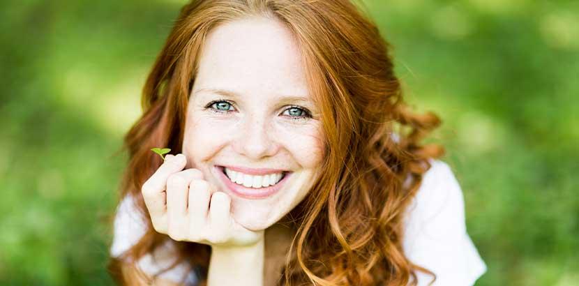 Junge hübsche Frau mit langen roten Haaren, die ihr strahlendes Lächeln als Ergebnis der ästhetischen Zahnheilkunde präsentiert.