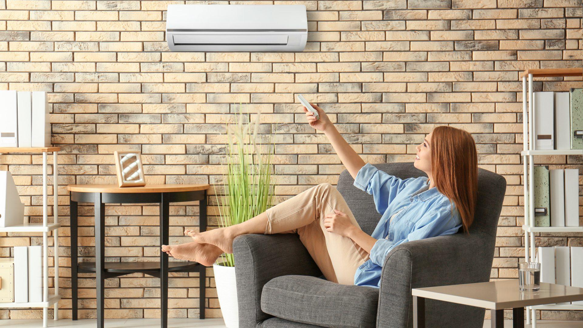junge barfüßige Frau schaltet die Klimaanlage ein während sie zuhause auf ihrem Sofa sitzt