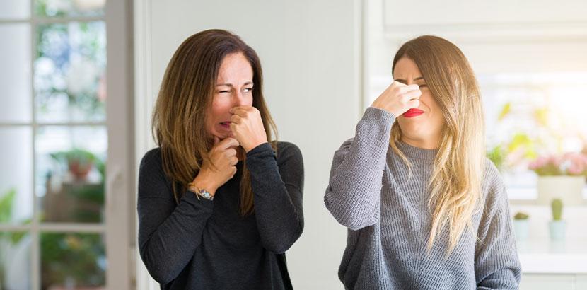 Zwei Frauen, die sich wegen des Rauchgeruchs in einer Wohnung die Nase zuhalten. Raucherwohnung renovieren.