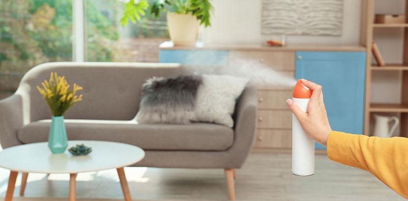Frau, die Geruchsneutralisierer in der Wohnung versprüht. Raucherwohnung renovieren.