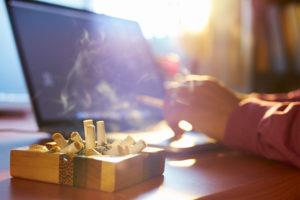Mann, der in der Wohnung raucht, ein voller Aschenbecher ist im Vordergrund. Raucherwohnung sanieren.
