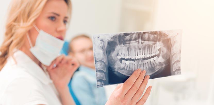 Eine Ärztin, die eine Röntgen Aufnahme vom Mund des Patienten gut betrachtet.