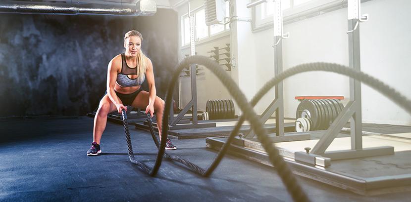 Crossfit was anziehen: eine Frau in kurzer Sportkleidung trainiert mit Seilen.