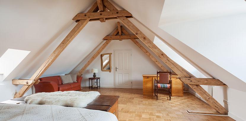 Schlafzimmer in einem ausgebauten Dachgeschoss. Dachstuhl anheben Kosten.