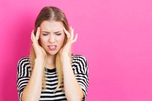 Junge Frau vor pinkem Hintergrund, die sich wegen Kopfschmerzen die Schläfen reibt. Hausmittel gegen Kopfschmerzen gefragt!