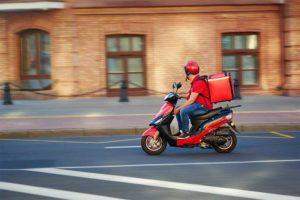 Lieferbote mit Fastfood auf dem Moped. Lieferdienste Lieferservice Österreich.
