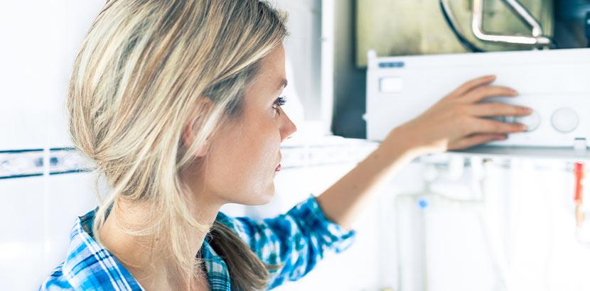 Hübsche junge blonde Frau, die einen Warmwasserboiler austauschen will.