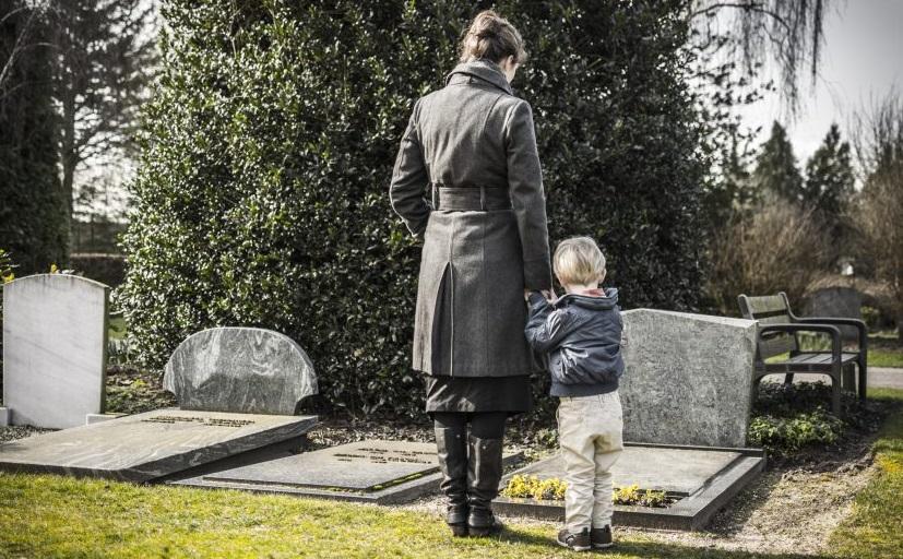 Junge Mutter mit ihrer Tochter, die am Friedhof am Grab eines Verwandten stehen, Rückenansicht. Bestattungskosten Wien.