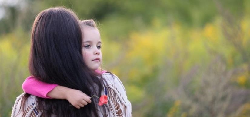 Kleines Mädchen im Arm seiner Mutter, das eine rote Mohnblume in der Hand hält und traurig schaut. Bestattungskosten Wien.