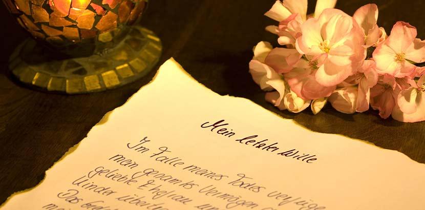 Handschriftlich verfasste Bestattungsverfügung, die auf einem dunklen Holztisch liegt.