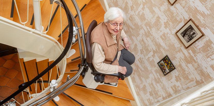 Ältere Dame, die eine kurvige Treppe mit einem Sitzlift (Treppenlift) überwindet.