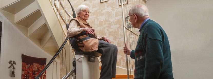 Älteres Ehepaar, von dem die Frau in einem Treppenlift sitzt und die Wendeltreppe hochfährt.