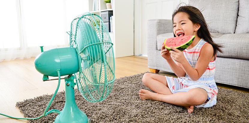 Ein junges Mädchen kühlt ihren Kopf und verbringt Zeit vor dem Ventilator.