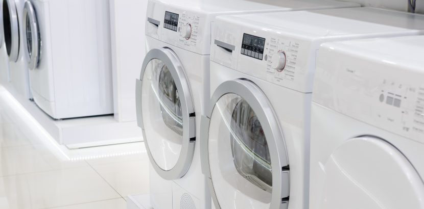 zwei weiße Waschmaschinen und ein Trockner