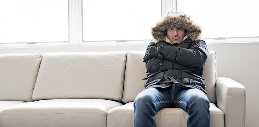 Mann, der in dicker Winterjacke auf dem Sofa sitzt und friert, weil ihm das Heizöl ausgegangen ist. Heizöl Notdienst.