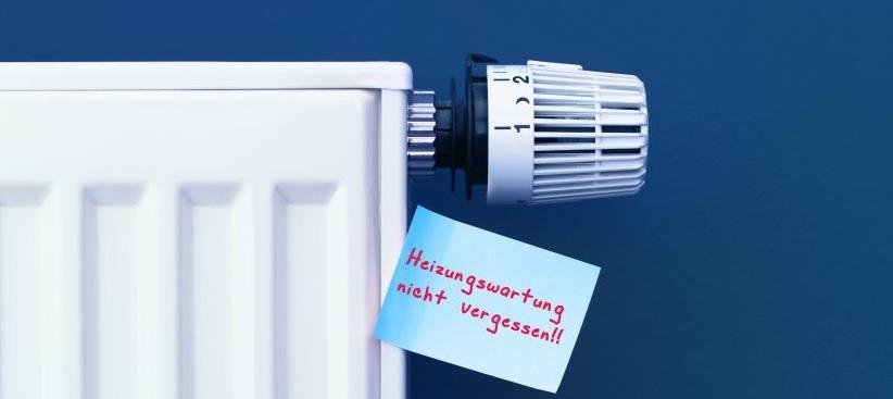 Weiße Heizung vor blauer Wand mit einem Zettel dran, auf dem Heizungsservice zu lesen ist.