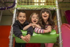 Zwei Mädchen und ein Junge, die Spaß im Indoorspielplatz haben.