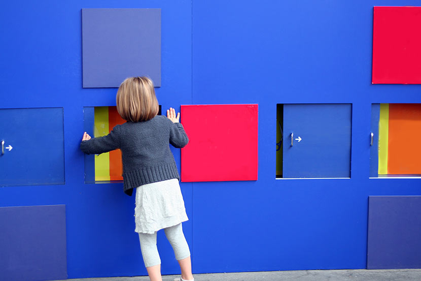 Ein Mädchen steht vor einer Mitmach-Wand im Kindermuseum.