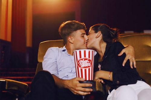 Junges Pärchen, das sich im Kino einen Film anschaut und sich küsst. Kinos Wien.