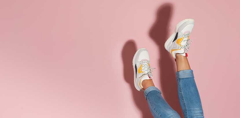 Frauenfüße mit coolen Sneakers vor einem rosa Hintergrund. Sneakers Wien.