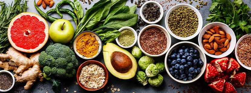 Ein Tisch voll mit Superfood: Chia, Goji, Avocado, Grapefruit, Gemüse, Beeren, Nüsse, Heidelbeeren, Broccoli, Acai